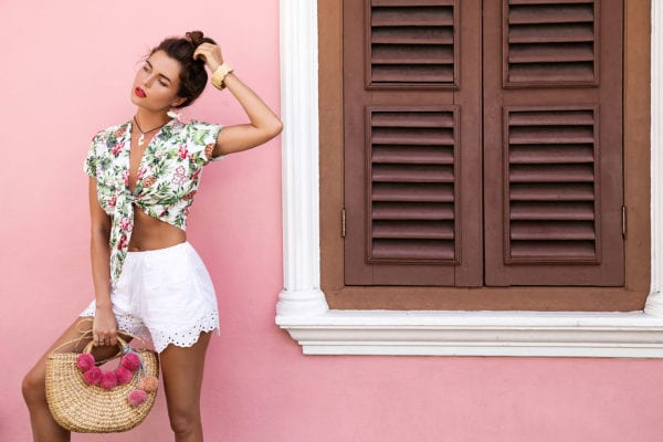 Sumer Bun Hair Styles -Beautiful woman posing beside the house with a pink wall
