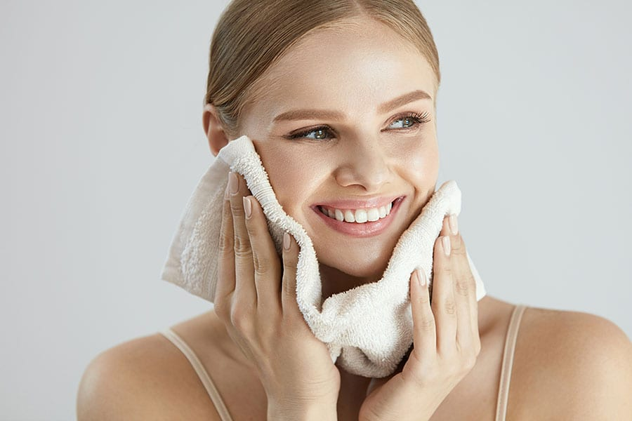 woman moisturizing her skin to care for oily skin in winter months