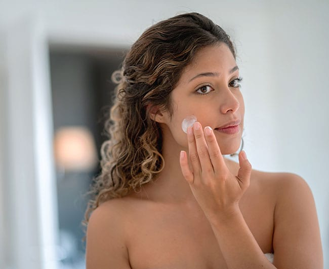 girl wondering, what is normal skin? She is looking in the mirror as she applies skin moisturizer