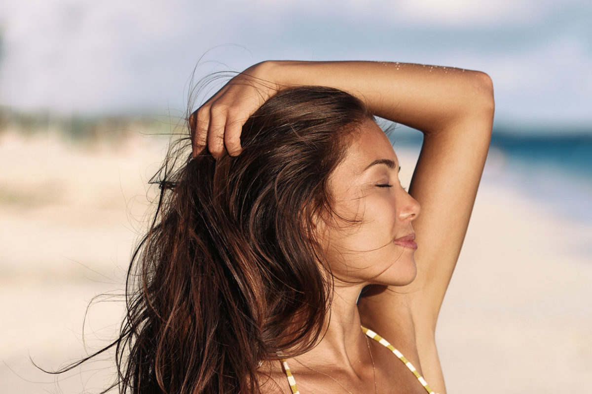10 Tips for Summer Oily Skin. Photo of young woman on beach in the sun.